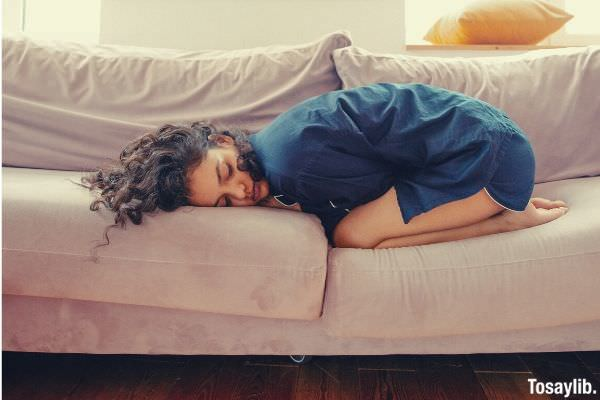 woman lying on the sofa blue clothes and curly hair