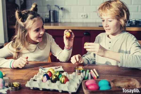 children boy and girl decorating eggs on the table