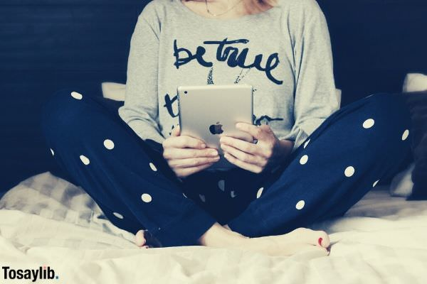 girl sitting using ipad staying at home on a bed