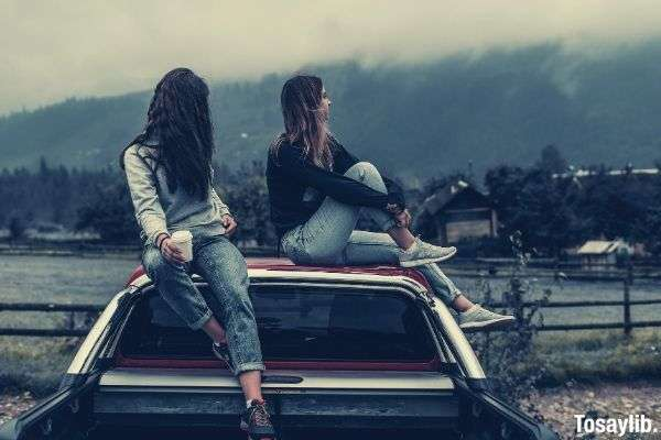 two women sitting on vehicle roofs pick up truck
