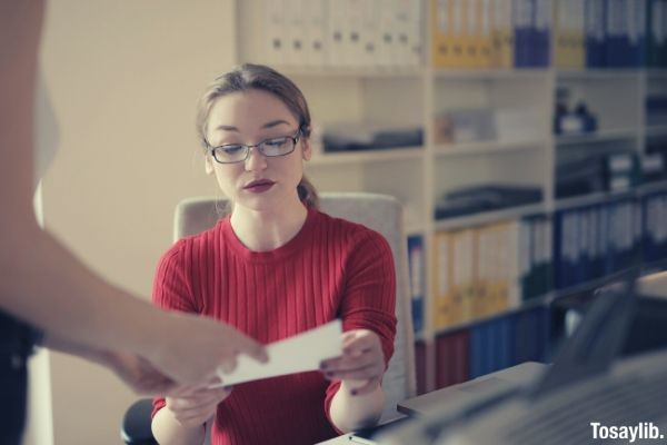 woman in red crew neck t shirt wearing eyeglasses examining documents