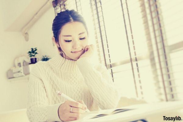 image of a woman wearing white sweater holding pen writing on a notebook