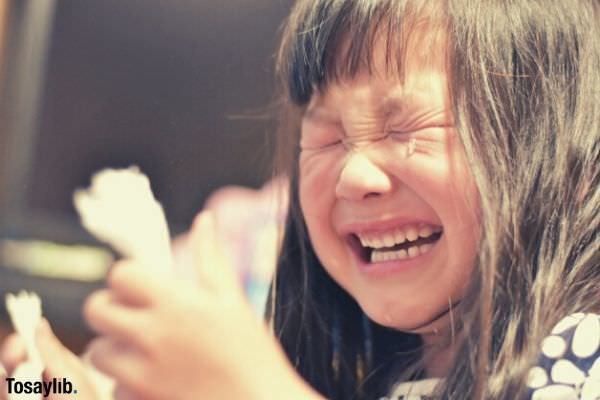 child girl long hair crying holding tissue paper