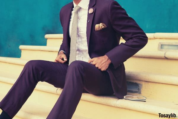 person sitting on stairs wearing formal maroon suit beside sunglasses