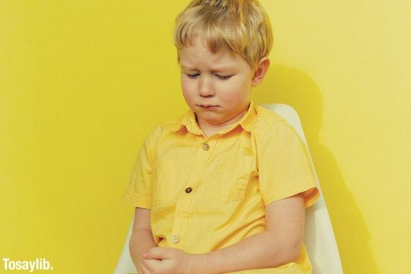 kid in yellow clothes sitting on white chair yellow wall