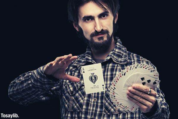 man holding card fan card tricks black background
