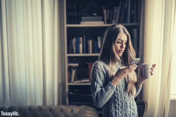 photo of woman in gray sweater holding white ceramic cup while using her phone
