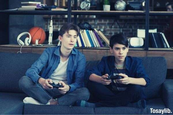 two brothers sitting at the sofa while playing video game