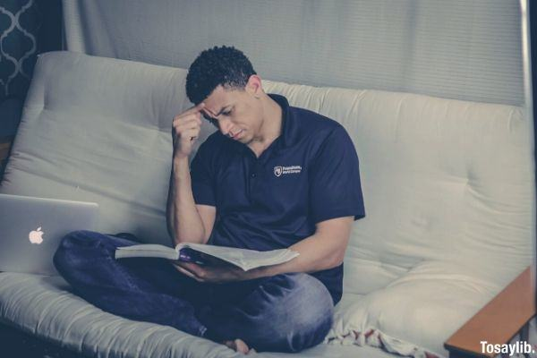 man sitting on the sofa reading book while touching his head