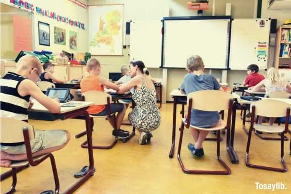 children sitting on brown chairs inside the classroom writing teacher helping whiteboard letters