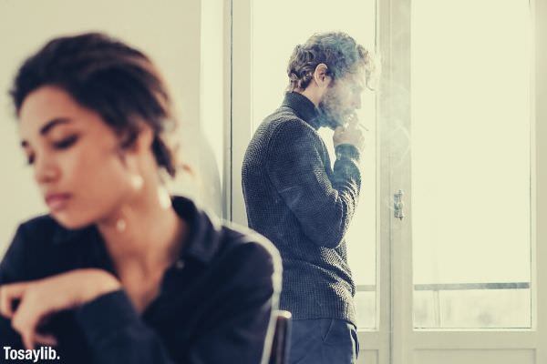 couple having a misunderstanding man having cigarette near the window
