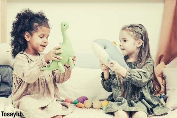 two girls playing stuffed toys dinosaur and whale