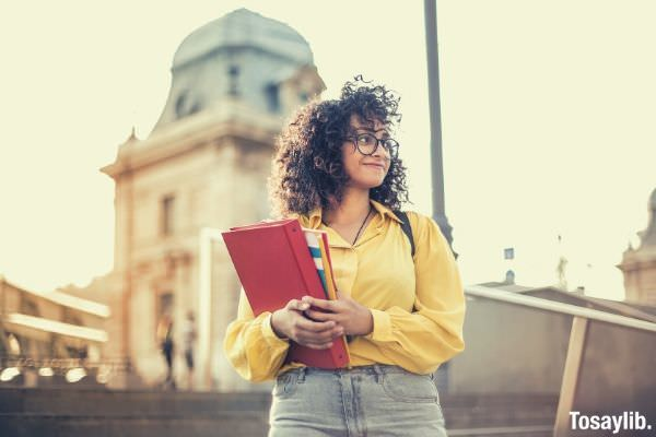 woman in yellow jacket holding a red book
