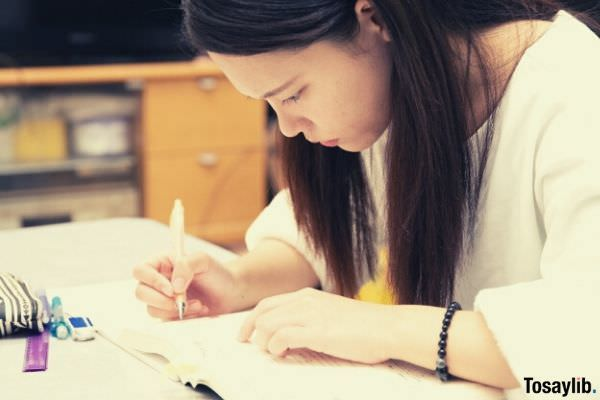 woman in white writing on her notebook using pen
