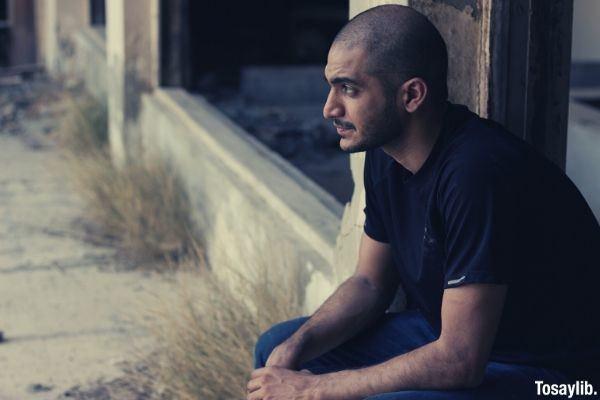bald man wearing black shirt sitting and thinking