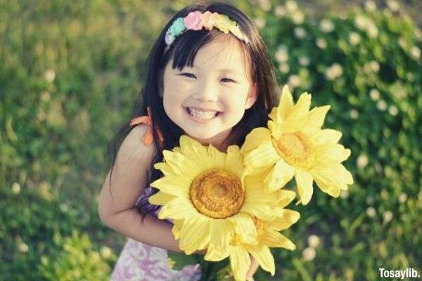 cute beautiful girl holding big sunflower smiling