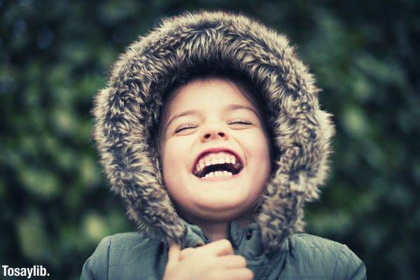 selective photography of a child wearing mink coat laughing