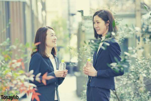 businesswomen chatting while holding water