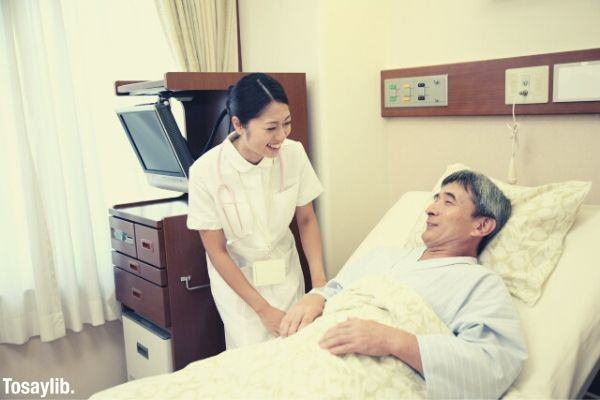nurse and a male patient lying on hospital bed