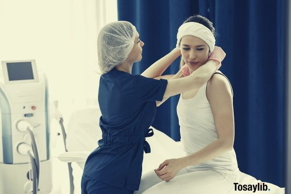 woman in blue scrub suit helping woman sitting on bed