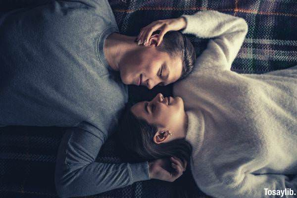 02 man and woman lying on bed wearing gray and white sweater