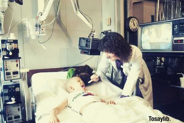 doctor woman checking up a child lying on bed