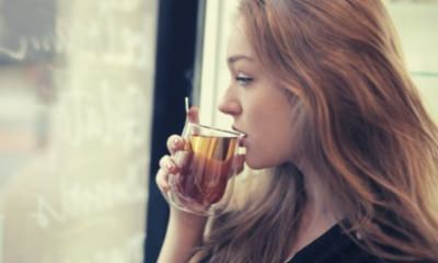 contemplating-with-brown-hair-woman-drinking-hot-tea-in-cafe
