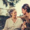 joyful-adult-daughter-greeting-happy-surprised-senior-mother-in-garden