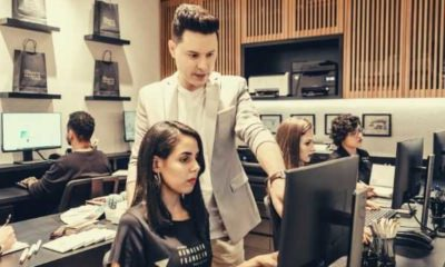 man-in-formal-suit-pointing-something-at-the-monitor-teaching-a-woman