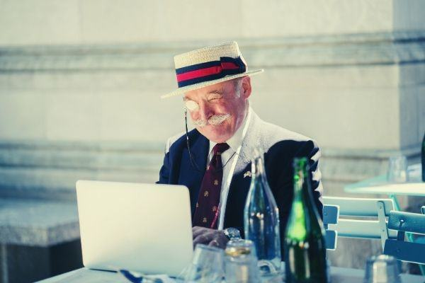 old-man-wearing-hat-and-monocle-using-laptop