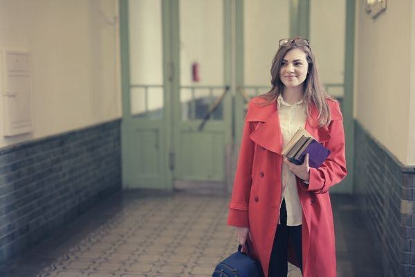 smart-female-student-with-books-and-backpack-in-university-hallway-pink-blazer