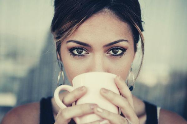 woman-drinking-coffee-on-a-white-coffee-mug-looking-at-the-camera