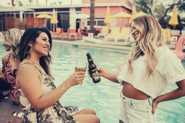 woman-on-pool-tossing-liquor-on-another-woman-wearing-hanging-white-shirt