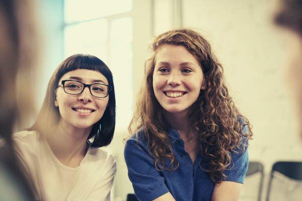 woman-wearing-blue-polo-shirt-beside-woman-wearing-white-shirt-and-glasses