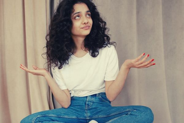 young-woman-with-curly-hair-sitting-on-white-table 2