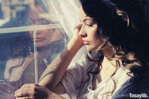 curly haired woman sitting beside the window