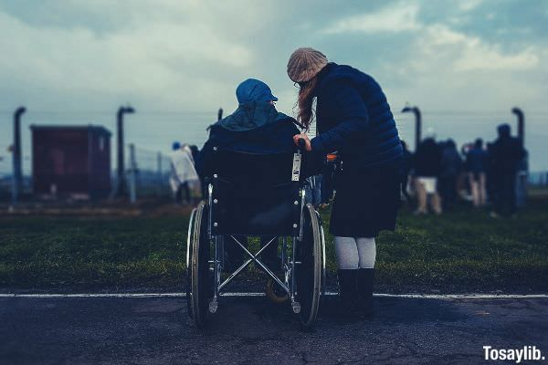 man sitting on the wheelchair while woman is standing beside him