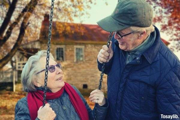 old happy couple woman sitting on swing while the man is standing happy