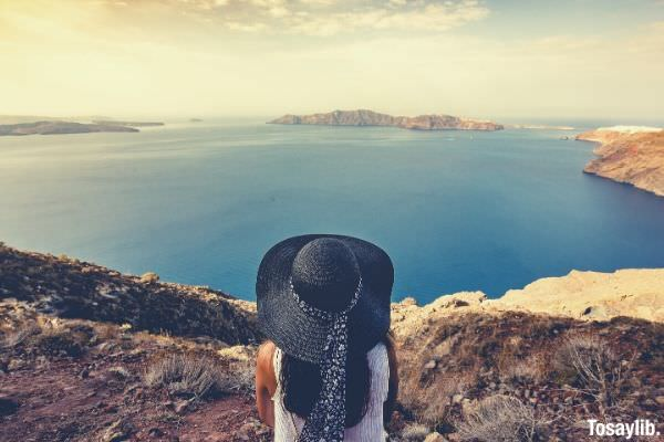 woman in black hat looking at the lake