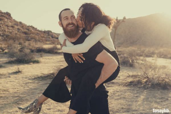 woman in white long sleeves and black pants kissing while on the back of the man in black shirt