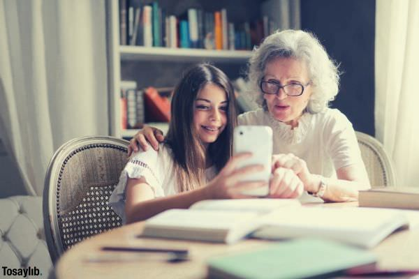 photo of woman showing her cellphone to her grandmother sitting on the chair table books