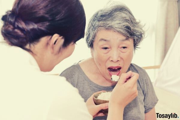 caregiver spoon feeding her white haired patient