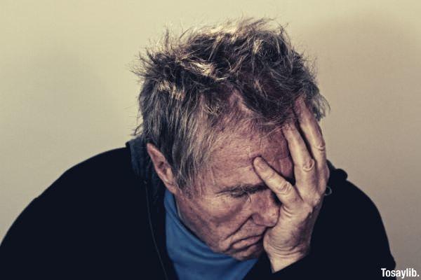 old man headache depressed wearing black sweater holding his head