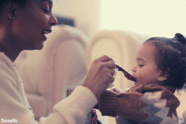 photo of woman feeding her child