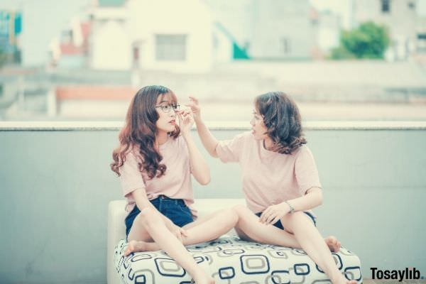 two young women sitting on couch beside each other wearing pink shirt and blue short jeans
