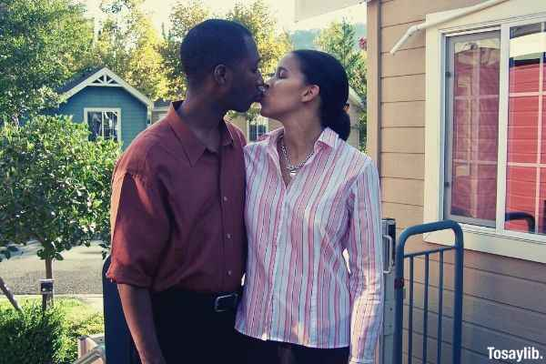 husband in red polo kissing wife in stripe blouse outside the house