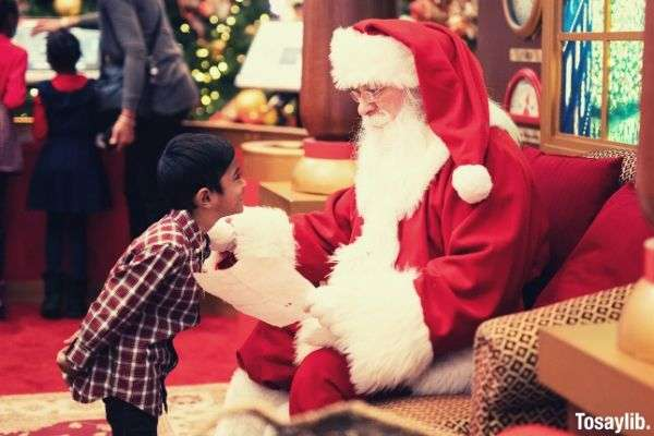 boy standing in front of a man wearing santa claus costume