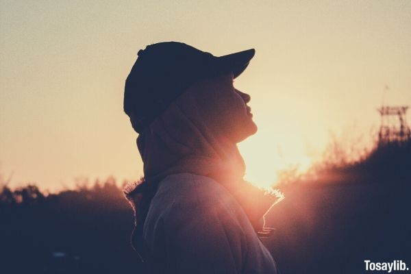 photo of a woman wearing cap silhouette sunset