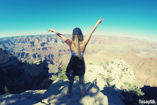 woman in tank top with cap raising her hand on top of concrete beautiful view