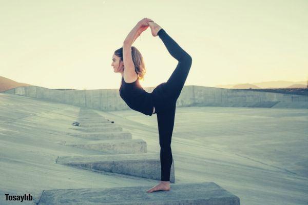 woman stretching black pants sando sky